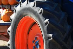 Close up of isolated black wheel tire with deep sufficient tread of antique old tractor with red rim and blue nuts on a farm in royalty free stock photography