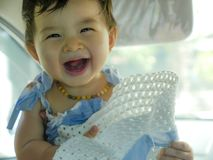 Close up isolated face portrait of sweet and adorable Asian Chinese baby girl laughing and smiling cheerful holding hat enjoying royalty free stock image