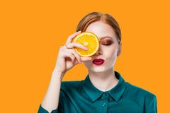 Beautiful redhead girl with professional makeup. Close up isolated portrait of young redhead woman holding halved oranges at her eyes. Human face expressions and Stock Photo