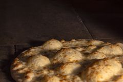 Close up of Italian bread roll with olive oil roasted in a stone oven. royalty free stock image