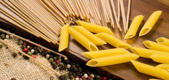 Close up of Italian spaghetti and pasta with decorative pepper on a wooden board and canvas Royalty Free Stock Images