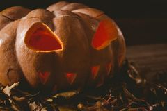 Close up of jack o lantern with leaves on table during autumn Stock Photo