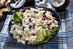 Close-up of Jamaican Rice and Red Beans. Cooked with coconut milk seasoned with garlic, onions and creole spice in a bowl with ingredients at the background royalty free stock photos