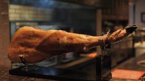 Close-up jamon Professionele snijders snijdende plakken van een gehele bone-in serranoham stock video