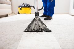 Janitor Cleaning Carpet With Vacuum Cleaner. Close-up Of A Janitor Cleaning Carpet With Vacuum Cleaner At Home royalty free stock photography