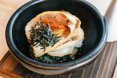 Close up Japanese Chashu Don: Steam Rice topping with Roasted Pork Belly, Yolk, Dried Seaweed and Saffron. Served in black ceramic bowl with Shoyu sauce stock image
