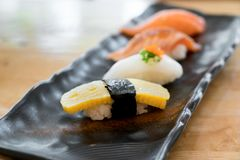 Close up of japanese cuisines nigiri sushi set on black plate se Stock Photos