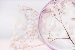 Close up of Jar with cosmetic cream and flowers , natural cosmetic product or beauty concept on pastel background. Front view stock image