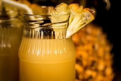 Pineapple juice and slice placed on a wooden table. Close-up of jars of pulpy fresh pineapple juice and pineapple slices placed on a wooden table. Summer drink Royalty Free Stock Photos