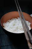 Close up Jasmine Rice in Bowl with Chopstick. On black bamboo mat background stock photos