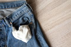 Close up jeans front pocket, turning out the empty pockets with. No money on wooden ground texture background with copy space royalty free stock photos