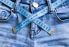 Close up jeans and soft meter waist measurement. Close up jeans and soft meter, waist measurement. diet. fitness. lose weight royalty free stock photo
