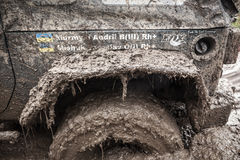 Close up of  Jeep wheel stuck in a deep muddy pit. Stock Photo