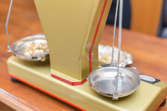 Close-up of jewelry scale. Close-up of an old-fashioned jewelry scale, while it's weighting some gold objects royalty free stock images