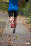 Close Up Of Jogger's Feet Running On Path. With Leaves Royalty Free Stock Photos
