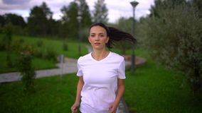 Close up of jogging beautiful young woman in slow motion. Fit girl run outdoors. Close up of fitness woman run on park. stock video footage