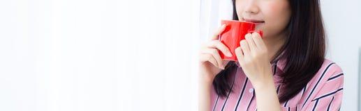 Close-up jonge Aziatische vrouw met drank een kop van het vensterachtergrond van het koffie bevindende gordijn in slaapkamer stock fotografie