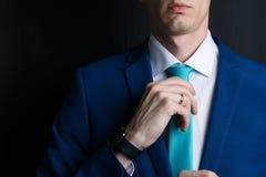 Close-up jonge mens in een kostuum Hij is in een wit overhemd met een band De man maakt zijn band recht royalty-vrije stock afbeeldingen