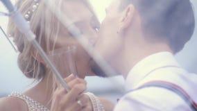Close-up, Jonge mooie jonggehuwdenkus onder een transparante paraplu De zonnige dag van de lente Huwelijk stock video