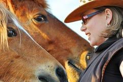 Close-up jonge mooie vrouw die aan twee paarden spreken stock afbeelding