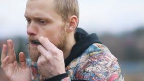 Close-up jonge slimme mens met het beige baard spelen op lippen muzikaal instrument in landschap van platteland, Regelmatige nok stock video
