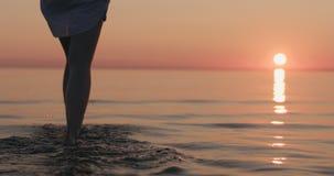 Close-up jonge vrouwelijke benen die in ondiep water op een strand lopen stock foto