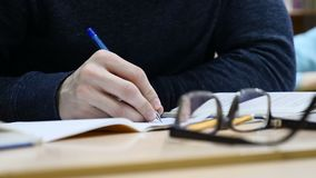 Close up of male journalist`s hands hold pen making notes at press conference. Looking glasses on table. stock footage