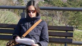 Close up: Jovem mulher que senta-se em um banco e que lê no parque Fortaleza de Petrovaradin, Novi Sad, Sérvia video estoque