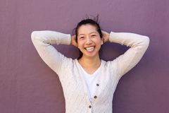 Close up joyful asian woman standing with hands behind head Royalty Free Stock Photo