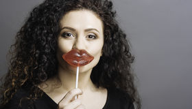 Close up of joyful girl holding candy. Good mood. Portrait of pretty brown-eyed woman holding lollypop in front of her lips looking straight at camera, standing Stock Photos