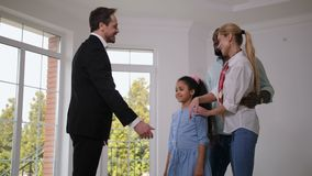 Broker giving house keys to happy little homeowner stock video footage
