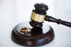 Close up of Judge gavel deciding on marriage divorce and two golden marriage ring.  royalty free stock images