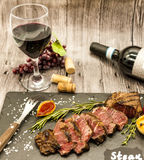 Close-up of juicy beef steak striplon with a bottle and a glass of red wine on a black stone plate on a wooden table. Royalty Free Stock Photo