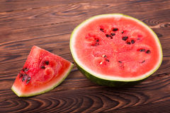 Close-up of juicy organic watermelon on the wooden background. The pulp of watermelon is sweet and the rind is green. Summer fruit. A slice and a half of a stock photos