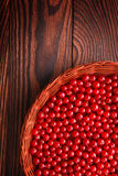 Close-up of juicy red currants on a brown background. A basket filled with tasty currant. Nutritious organic berries. Stock Photography