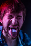 Close-up on junkie man taking LSD Stock Images