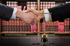 Justice Scale With Judge And Client Shaking Hands. Close-up Of A Justice Scale With Judge And Client Shaking Hands In A Courtroom Royalty Free Stock Photography