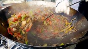 Close-up4k lengte die van professionele kok en groenten en vlees in grote pan op openlucht culinair bewegen mengen stock videobeelden