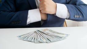 Close-up4k lengte van bedrijfs misdadig verbergend kanon in jasje en het bekijken grote stapel van geld voor hem stock footage
