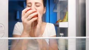 Close-up4k lengte van het jonge vrouw bekijken binnen van ijskast nacht en het bijten rode appel stock videobeelden