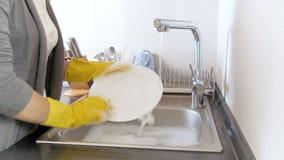 Close-up4k video van jonge vrouw in gele rubberhandschoenen die schotels op keuken wassen stock videobeelden