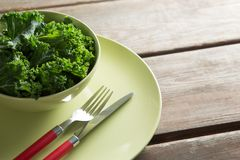 Close-up of kale in bowl on plate over table Stock Images