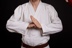 Close-up karate student on a black background. Fighter in uniform showing break sign. Karate lessons concept. stock photo