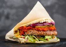 Minced meat kebab, beef in flat cake with vegetable, red sauce. Greek gyros royalty free stock photos