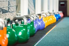 Close-up of kettlebells of various weights and colors. Close-up of metallic kettlebells of various weights and colors on the floor of a fitness club with modern Stock Images