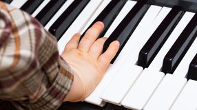 Close up of Keyboard of synthesizer and child hands Royalty Free Stock Photo