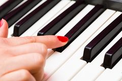 Close up of Keyboard of synthesizer and woman hands Royalty Free Stock Images