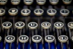 Close up of alphabet keys on a vintage manual typewriter. Close up of keys on a black vintage manual typewriter on a cobalt blue background royalty free stock image