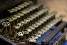 Close up of alphabet keys on a vintage manual typewriter. Close up of keys on a black vintage manual typewriter on a cobalt blue background royalty free stock images