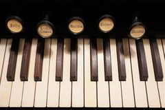 Close up of the keys and stops of an old pump organ. Close-up of the keys and stops of an antique pump organ circa 1850. The organ is from a small country church stock photography